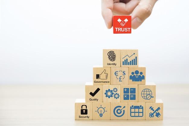 Hand kiezen vertrouwen pictogrammen op houten speelgoed blok. Premium Foto