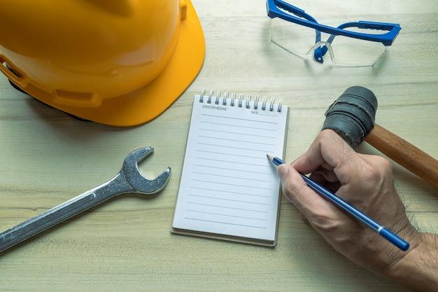 Hand mensen man met blocnote voor het controleren van fabriek of industrie op bureau voor het schrijven van notities inspecteur. Premium Foto