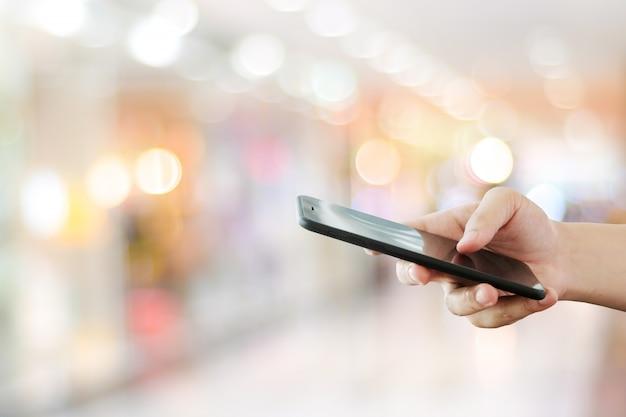 Hand met behulp van slimme telefoon over onscherpte bokeh licht, business en technologie, internet van dingen concept Premium Foto