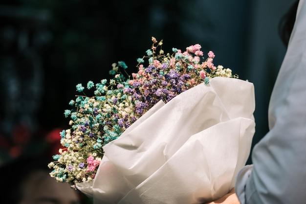 Hand met boeket van gedroogde gypsophila bloemen verpakt in papier Premium Foto
