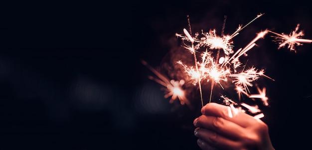 Hand met brandende sparkler ontploffing op een zwarte bokeh Premium Foto