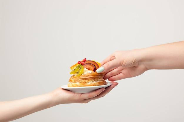 Hand met cake met vers fruit op grijs Gratis Foto