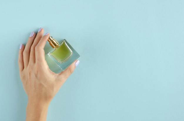 Hand met de samenstelling van de parfumfles op blauwe achtergrond. Premium Foto