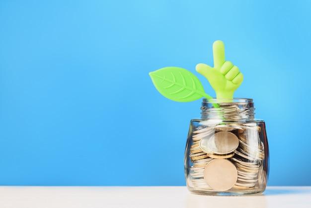 Hand met duim omhoog en blad op glazen pot met munten. investeringsgroei concept. Premium Foto