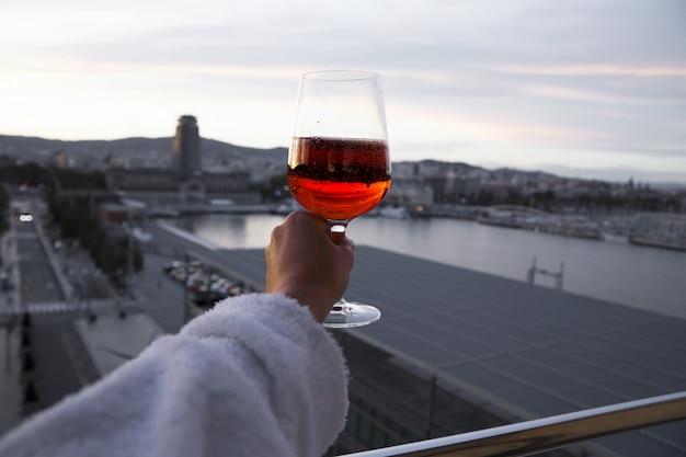 Hand met een glas rode wijn. uitzicht over de stad Premium Foto