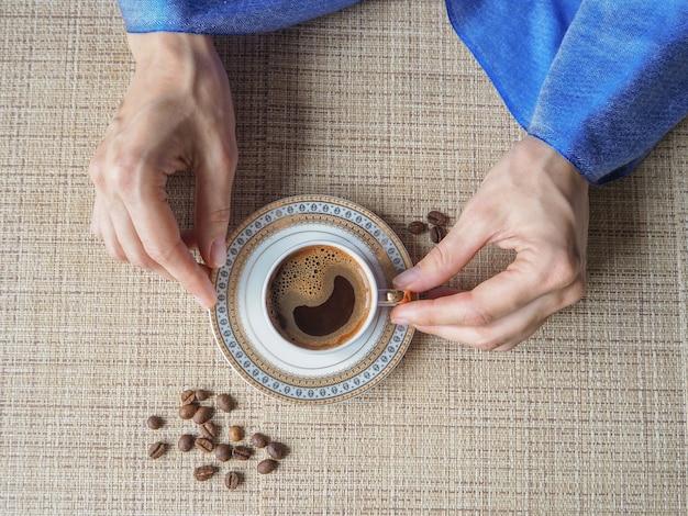 Hand met een kopje koffie. de hand houdt een elegante kop koffie. Premium Foto