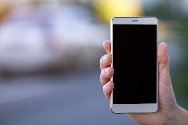 Hand met een mobiele telefoon met zwart scherm in de straat Premium Foto