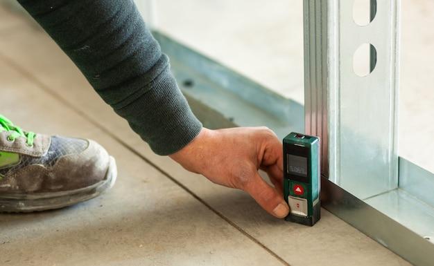 Hand met een nauwkeurige laser-meter op de vloer. Premium Foto