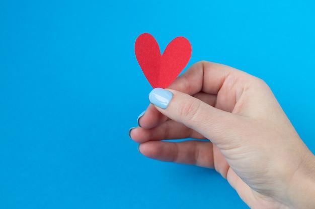 Hand met een rood hart op een blauwe achtergrond. achtergrond voor valentijnsdag Premium Foto