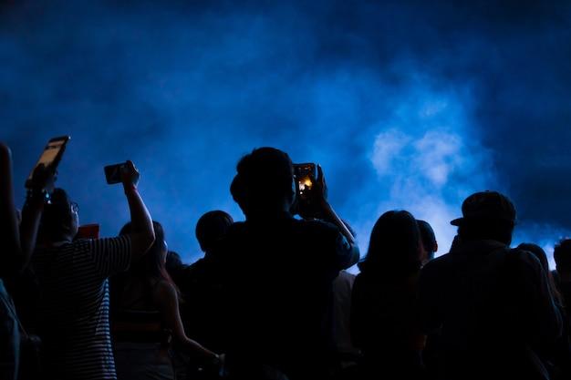 Hand met een smartphone neemt het festival van de livemuziek op, nemend foto van overlegstadium Premium Foto