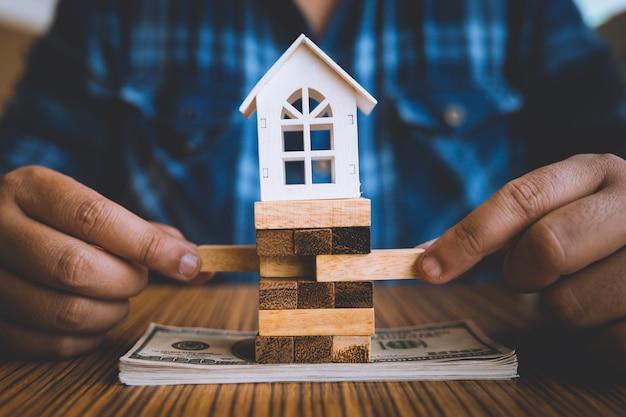 Hand met een stuk hout blok met model witte huis op dollar bankbiljet. Premium Foto