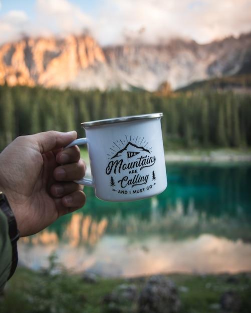 Hand met een witte mok met een wazig berglandschap als Gratis Foto