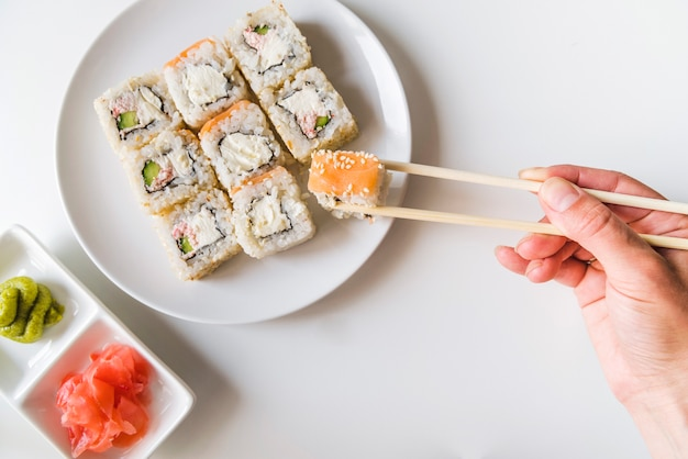 Hand met eetstokjes die een sushibroodje grijpen Gratis Foto