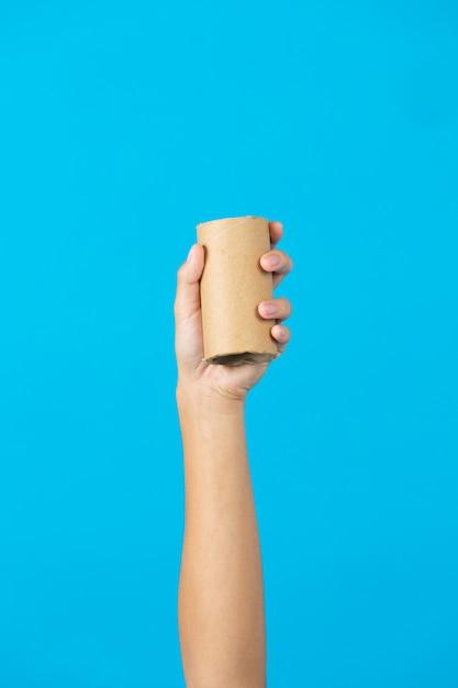 Hand met gebruikte papieren zakdoekje kern op blauwe achtergrond Gratis Foto
