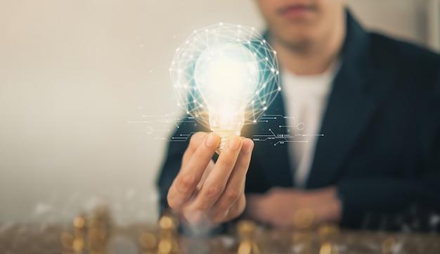 Hand met gloeilamp met innovatieve en creativiteit zijn sleutels tot succes. Premium Foto