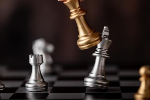 Hand met gouden koning aanval zilveren leider in het spel Premium Foto
