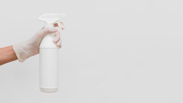 Hand met handschoen met reinigingsoplossing in fles met kopie ruimte Gratis Foto