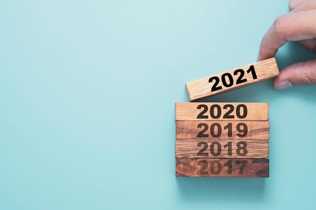 Hand met houten blokkubus die het scherm 2021 jaar afdrukt en boven het jaar 2020 met blauwe achtergrond neerzet. Premium Foto