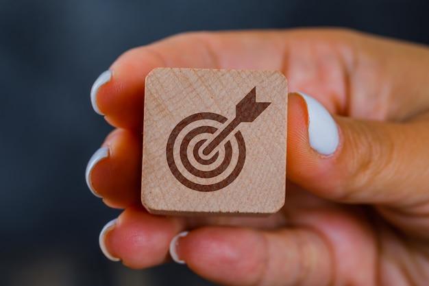 Hand met houten kubus met doel Gratis Foto