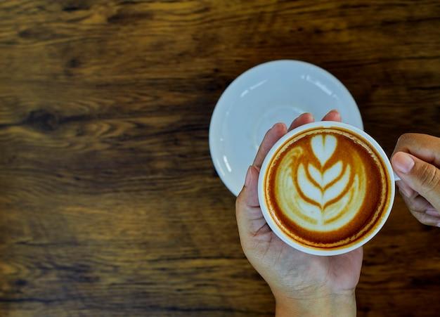Hand met koffiekopje op tafel Premium Foto