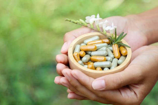 Hand met kruidensupplement van biologisch kruid Premium Foto