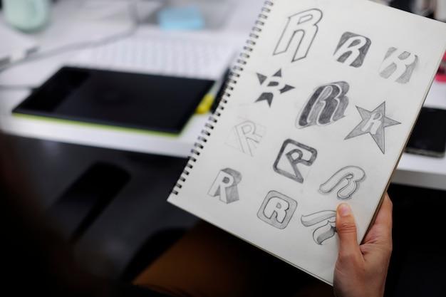 Hand met laptop met drew merklogo creatief ontwerp ideeën Gratis Foto