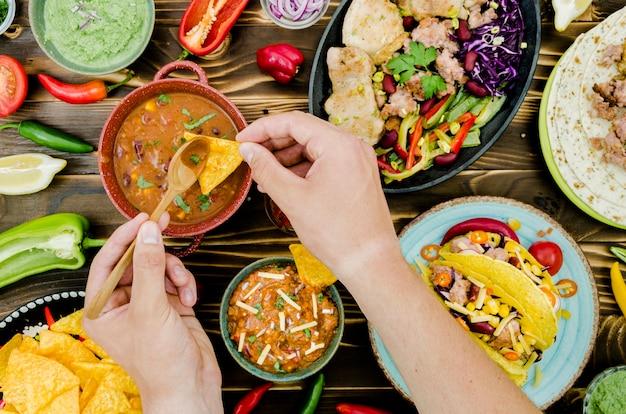 Hand met lepel en nacho in de buurt van mexicaans eten Gratis Foto