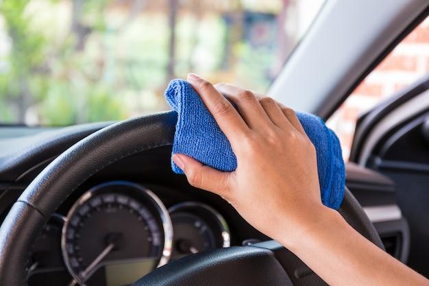 Hand met microfiber doekreiniging interieur en moderne auto op stuurwiel. Premium Foto