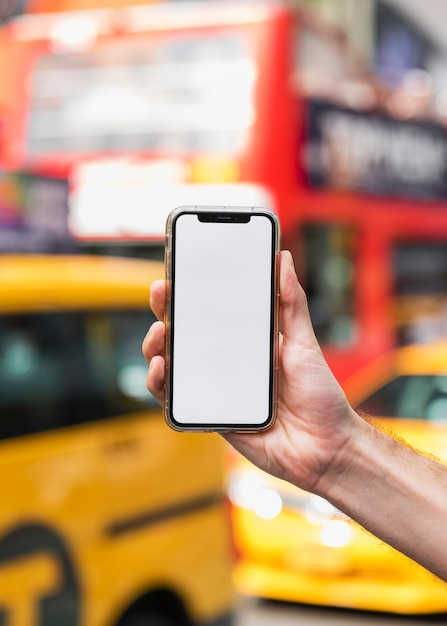 Hand met mobiel op onscherpe achtergrond Gratis Foto