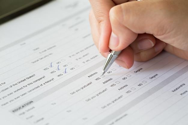 Hand met pen over blanco cheque dozen in aanvraagformulier Gratis Foto