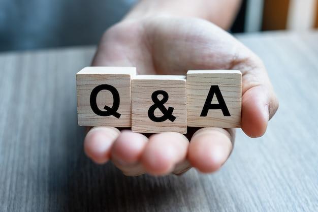 Hand met q&a houten kubusblok Premium Foto