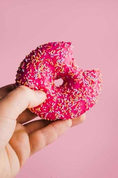 Hand met roze geglazuurde donut Gratis Foto