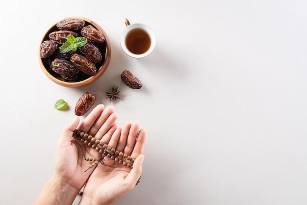Hand met rozenkrans en datum fruit voor ramadan muur Premium Foto