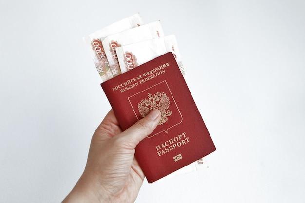 Hand met russisch paspoort met bankbiljetten van 5000 roebel Gratis Foto