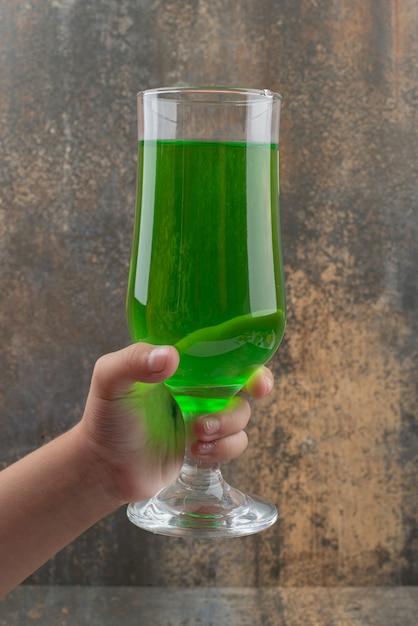 Hand met s glas sappige groene limonade op marmeren oppervlak Gratis Foto