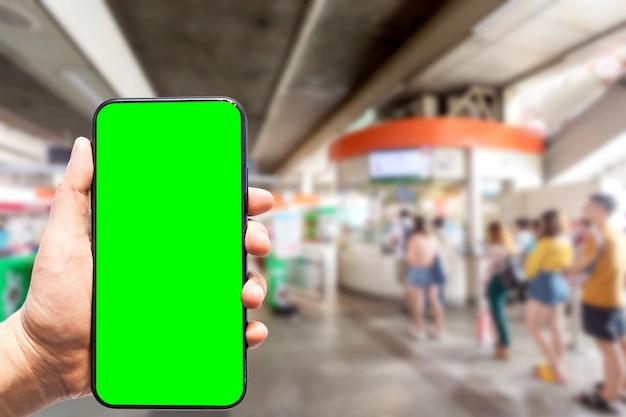 Hand met smartphone met groen scherm Premium Foto