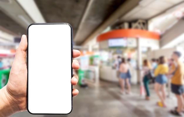Hand met smartphone wazig beelden aanraking van abstracte vervaging van mensen passagier staan in de rij wachtrij en wachten op de automatische toegangsdeur voor de trein bij de sky train station wazige achtergrond. Premium Foto