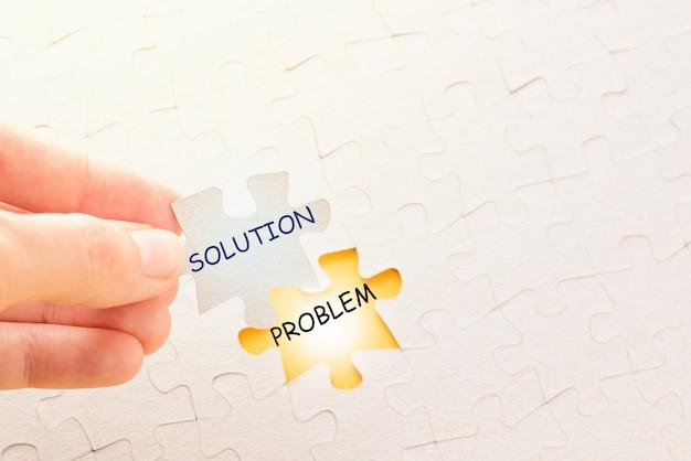 Hand met stuk van de puzzel met woord oplossing en zet het op zijn plaats met probleem Premium Foto