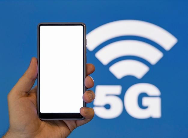 Hand met telefoon met 5g symbool achtergrond Gratis Foto
