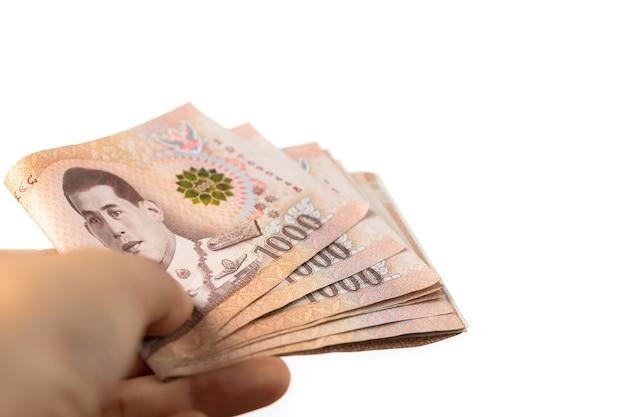 Hand met thaise munt, 1000 baht, geldbankbiljet van thailand op witte muur voor zaken en financiën concept Premium Foto