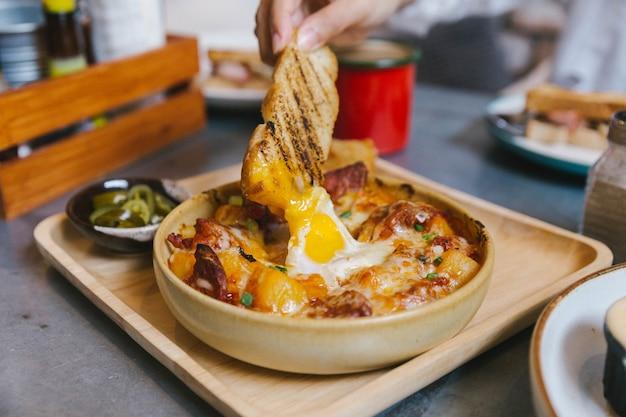 Hand met toast dompelen in cheesy ontbijt aardappelen met knapperige spek en gebakken ei. Premium Foto