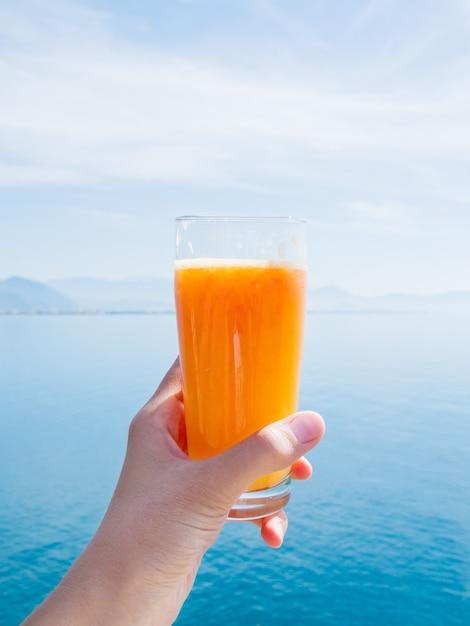 Hand met vers lekker vers geperst sap van rijpe sinaasappelen in glas. Premium Foto