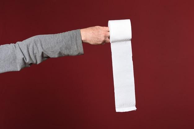 Hand met wc-papier op rode achtergrond Premium Foto