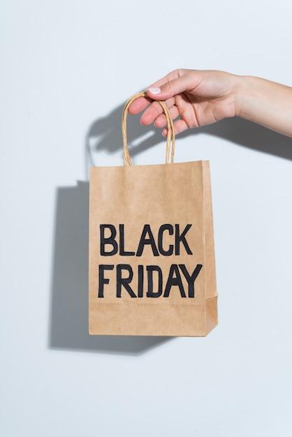 Hand met zwarte vrijdag papieren zak Gratis Foto