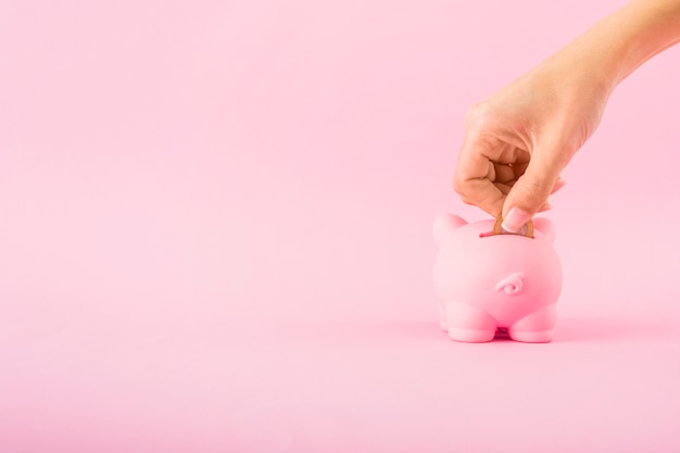 Hand munt aanbrengend roze spaarvarken Gratis Foto