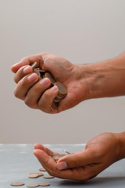 Hand munten in een andere gieten. Gratis Foto