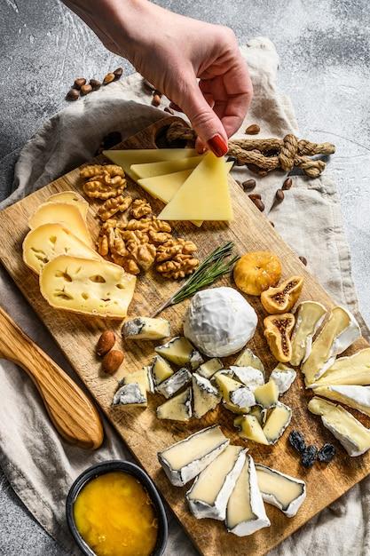 Hand neemt een stuk kaas van een kaasplateau geserveerd met noten en vijgen. grijze achtergrond. bovenaanzicht Premium Foto