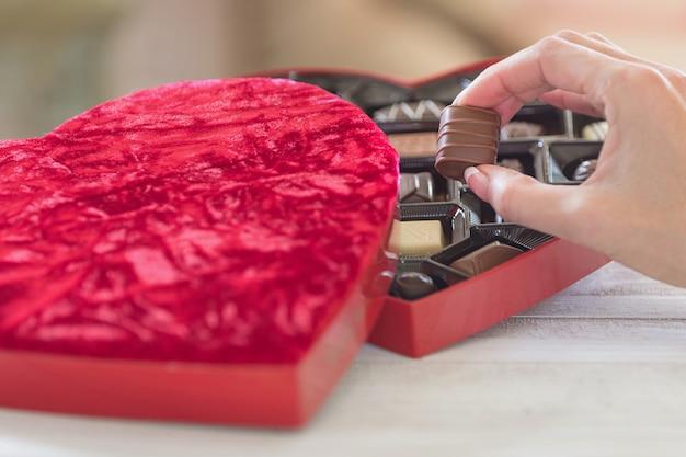 Hand nemen van een truffel van een hartvormige doos chocolaatjes Gratis Foto