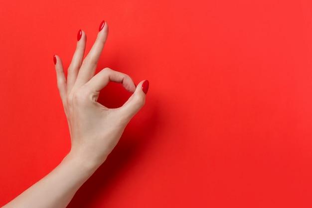 Hand ok-teken geïsoleerd op rode achtergrond Premium Foto