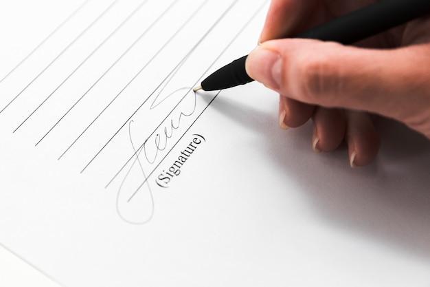 Hand ondertekening van een document met een pen Gratis Foto